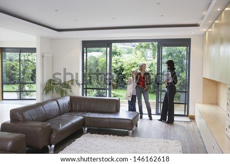 Full length of mother and daughter with female estate agent in new property - stock photo