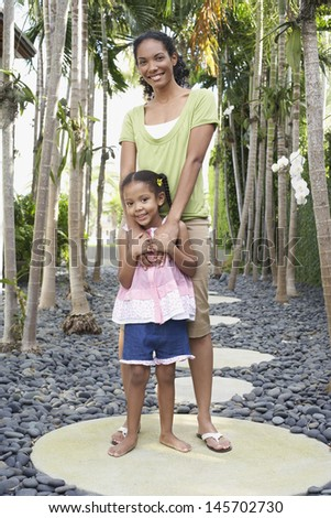 Full length of mother standing with arm around daughter on stepping stone - stock photo