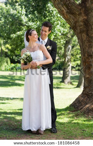 Full length of newly wed couple looking at each other while standing in park - stock photo