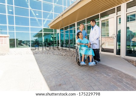 Full length of nurse and doctor looking at patient on wheelchair at hospital courtyard - stock photo
