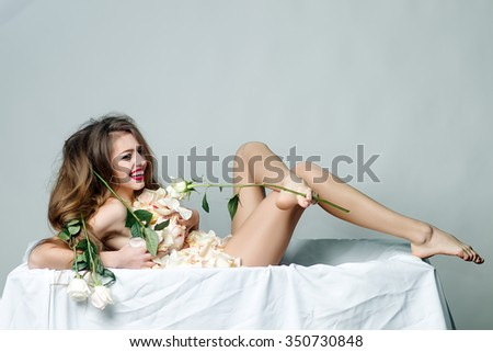 Full length of one beautiful naked happy smiling woman with straight slim undressed body and long hair lying in yellow flower petals on white fabric holding rose in raised leg in studio, horizontal - stock photo