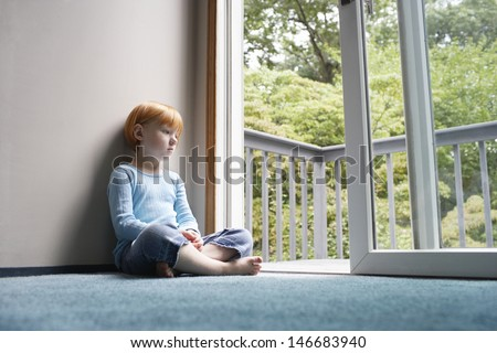 Full length of pensive young girl looking through balcony while sitting on carpet at home - stock photo