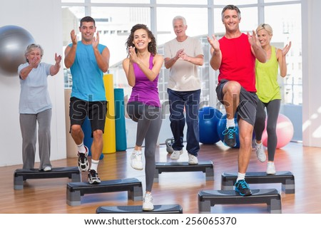 Full length of people performing step aerobics exercise in gym - stock photo