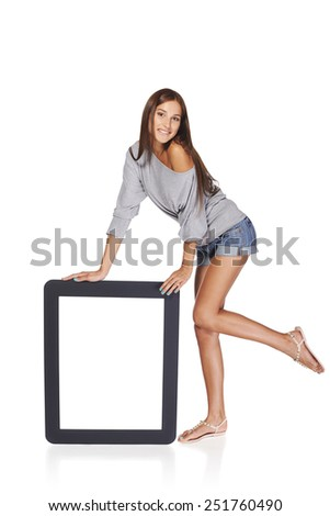 Full length of playful woman showing blank empty screen with copy space. Happy caucasian girl standing leaning at tablet frame over white background - stock photo