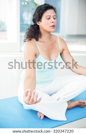 Full length of pregnant woman sitting in lotus pose with eyes closed on exercise mat at home - stock photo