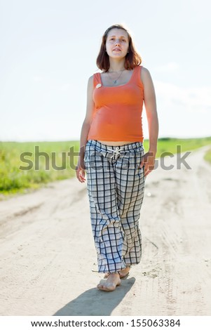 Full length of pregnant woman walking on  summer field