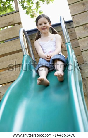 Full length of pretty young girl playing on slide in park - stock photo