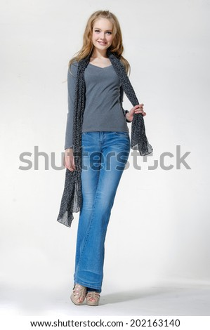 Full length of pretty young woman in jeans walking in studio  - stock photo