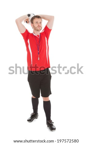 Full length of referee throwing soccer ball over while background - stock photo