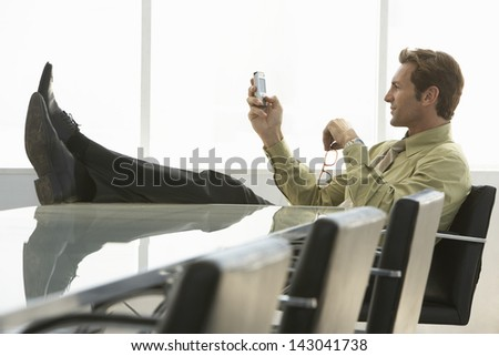 Full length of relaxed businessman with feet up text messaging on cell phone in conference room - stock photo