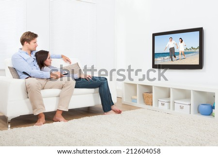 Full length of relaxed couple on sofa watching television at home - stock photo