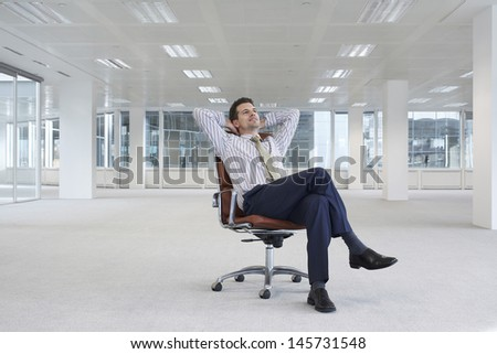Full length of relaxing young businessman on chair in empty office space - stock photo
