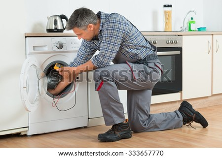 Full length of repairman checking washing machine with digital multimeter at home - stock photo