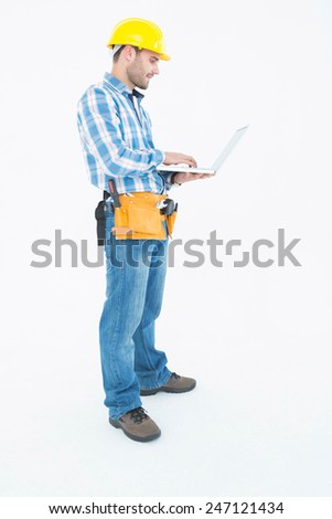 Full length of repairman using laptop against white background - stock photo