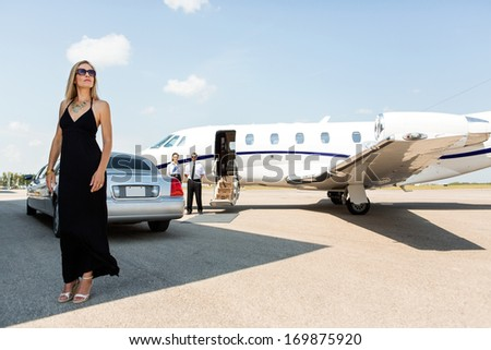 Full length of rich woman in elegant dress standing against limousine and private - stock photo