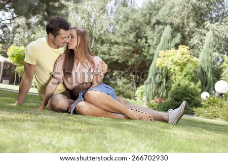 Full length of romantic young couple relaxing in park - stock photo