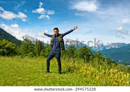 Full length of 20s man wearing dark jeans, navy top and gillet with arms out-stretched standing on grass. Snow-capped mountain vista and cloudy blue sky backdrop - stock photo