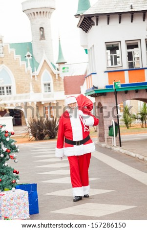 Full length of Santa Claus carrying bag while walking in courtyard - stock photo
