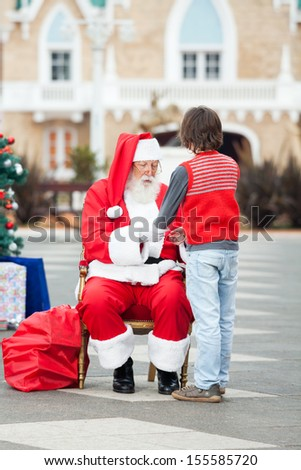 Full length of Santa Claus holding boy's hands in courtyard - stock photo
