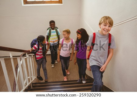 Full length of school kids walking up stairs in the school - stock photo