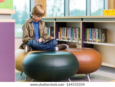 Full length of schoolboy using digital tablet on seat in library - stock photo
