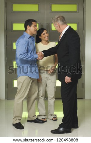 Full length of senior businessman shaking hands with hispanic couple in office