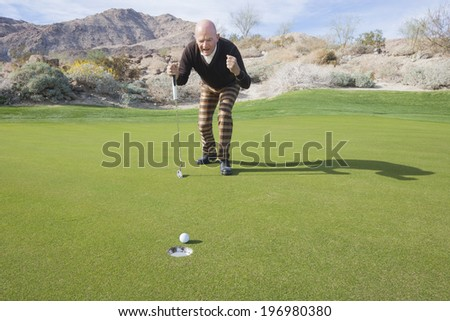 Full length of senior male golfer celebrating a putt at golf course - stock photo