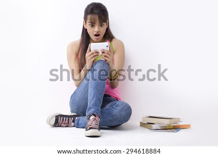 Full length of shocked female college student reading text message - stock photo