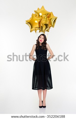 Full length of shy cute beautiful curly young female in retro style hiding star shaped balloons behind herself