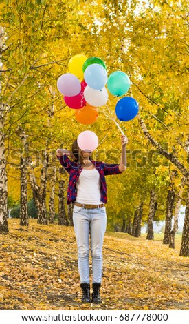 Full length of slim brown hair girl, dressed in casual dress style, yellow forest park background in perspective. Copy space for inscription. Young adult woman. balloon closed face