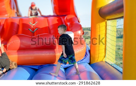 Full length of small boy (6-8 years) wearing t-shirt and multi-colored shorts walking in bare feet across blue base of multi-colored bouncy castle, children in background - stock photo