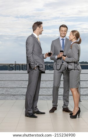 Full length of smiling businesspeople with wineglasses standing on terrace - stock photo