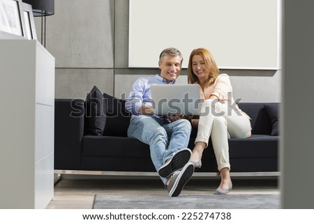 Full-length of smiling couple using laptop on sofa - stock photo