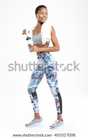 Full length of smiling cute young african american sportswoman standing and holding bottle of water over white background - stock photo