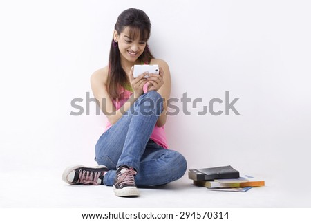 Full length of smiling female college student reading text message - stock photo