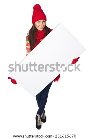 Full length of smiling happy woman in winter clothing holding white banner over white studio background. High angle view - stock photo