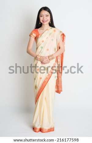 Full length of smiling mixed race Asian Indian girl standing on plain background. - stock photo