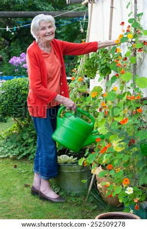 Full Length of Smiling Old Woman at the Flower Garden with Watering Can  Looking at the Camera. - stock photo
