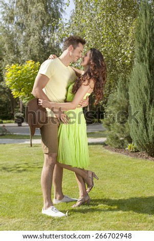 Full length of smiling young couple embracing in park - stock photo