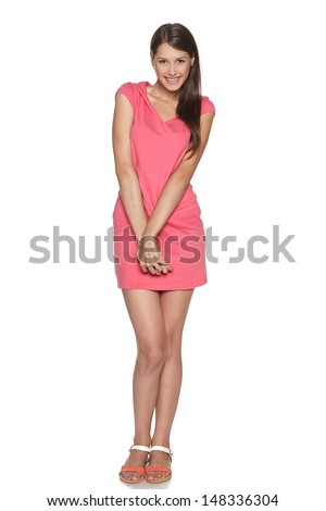 Full length of smiling young female feeling uncomfortable and shy isolated against a white background - stock photo