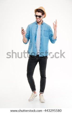 Full length of smiling young man listening to music from smartphone over white background - stock photo