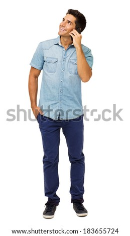 Full length of smiling young man looking away while answering smart phone against white background. Vertical shot. - stock photo