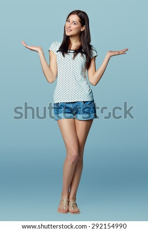Full length of smiling young slim tanned female in denim shorts shrugging her shoulders, on a blue background - stock photo