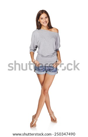 Full length of smiling young slim tanned female in denim shorts standing with crossed legs, isolated on white background - stock photo