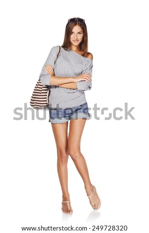 Full length of smiling young slim tanned female in denim shorts with backpack and sunglasses, isolated on white background - stock photo