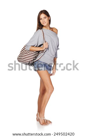 Full length of smiling young slim tanned female in denim shorts with beach bag, isolated on white background - stock photo
