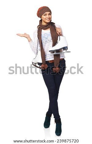 Full length of smiling young woman wearing clothing carrying a pair of ice skates and showing blank copy space, over white background - stock photo
