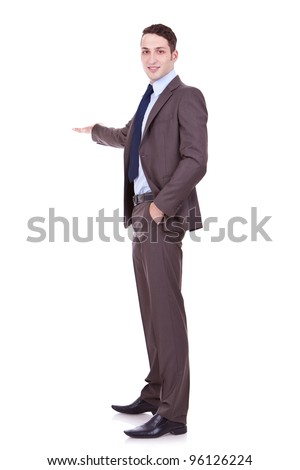 Full length of successful business man presenting over white background . young business man making a presentation and showing something - stock photo