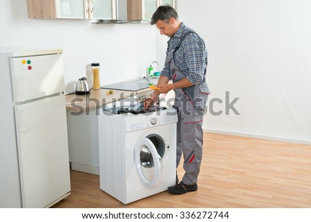 Full length of technician checking washing machine with digital multimeter in kitchen - stock photo