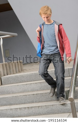 Full length of teenage student walking down university stairs - stock photo